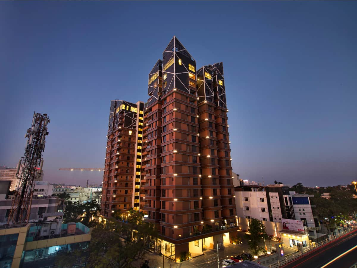 The façade of the building is designed distinctively to stand out as an edifice in Central Chennai. Formal & simple in aesthetics defined by warm woody hues and horizontal bands at its lower levels capped glamorously with four strong geometric patterns throwing beautiful light patterns from carefully embedded LED strips, the edifice brighter up the neighbourhood<br>Landmark Vertica, Chennai; Kembhavi Architecture Foundation <br> photographs: Sanjay Ramachandran